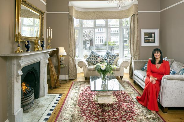 """Entrepreneur Rhoda McDonagh in her drawing room where she loves to light real fires. The sofas are from Caseys in Cork, the coffee table was bought in Castleisland, Co Kerry, and the harp is her own. """"I used to play for the guests in Dromoland and Adare"""", she explains. Photo: Tony Gavin"""