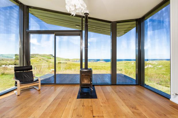 Floor to ceiling windows provide a panoramic view of the surrounding countryside and coastline