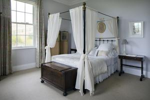 Maria Ines brought this antique four-poster  bed, which she has dressed with embroidered linen and lace, from her former home at Whitfield Court