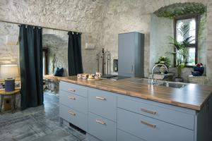 The kitchen is part of the great hall and the island contains everything hob, cooker, sink and storage