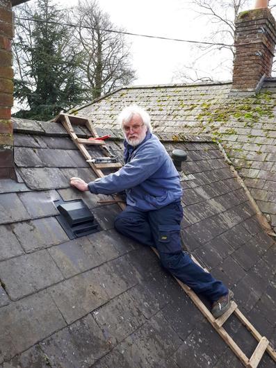 Peter Davitt fixing the roof of their other property