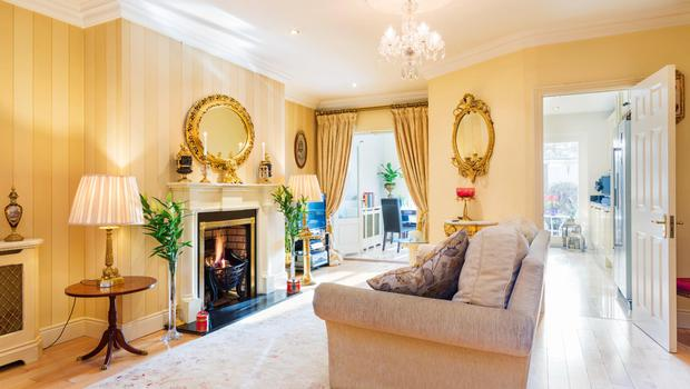 The maple-floored living room has a fireplace with a gas fire