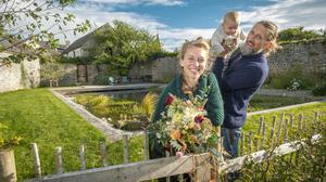 Cathal O'Meara with his wife Petra and baby Cliff at the award-winning natural swimming pool in their walled garden at Kilworth, Co Cork. Photo: Michael Mac Sweeney