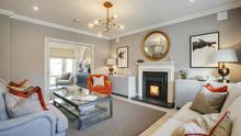 The main reception room which comes with original artwork, hand-made cushions, and a burnt-orange armchair which is complemented by matching cushions on the sofas