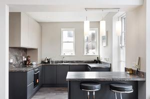 The kitchen has grey units