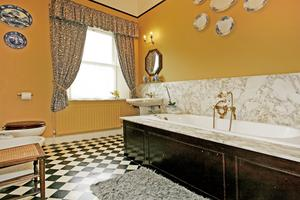 Family bathroom with marble-lined bath
