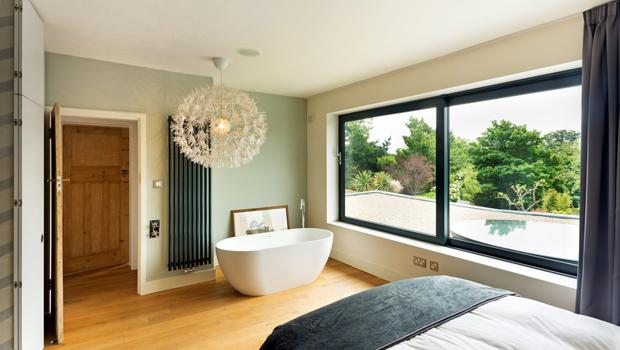 The master bedroom has a roll-top bath right in the room at the end of the bed, but also an ensuite with a dividing wall between the wc and shower, and a walk-in wardrobe.