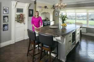 """Interior designer Michelle Keane in her kitchen, with its Amtico floor and units from local kitchen company Vaughans. The worktops are marble. As well as a four-oven Aga, she has a gas hob. """"I'm into cooking and the Aga is the best money you'll spend, if you're into it,"""" Michelle says"""