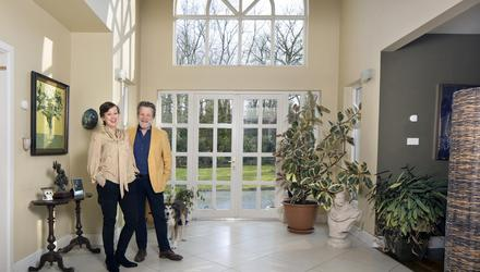 "Una Herlihy and Roger O'Reilly in their magnificent hall, the feature that first sold them on the house. It's designed like a cross, with the other downstairs rooms leading off it, so light floods in from all sides as well as via the massive windows. Beside them is their collie cross, Sammy. ""He was a rescue dog. We always say we don't know who rescued who — he's a little country gentleman,"" says Una, while Roger adds, ""He's too nice, a terrible guard dog"""