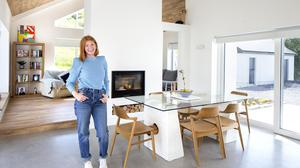"""Heather O'Malley in her open-plan dining room/kitchen, which is full of light with windows on two sides and a vaulted ceiling. A chimney divides this area from the sitting room. They were advised not to put in the wood-burning stove as they have underfloor heating but Heather says it's cosy on dull evenings. The glass table is from her old family home and holds lots of memories, particularly of her late mother — """"I wanted the table because I want this house to be a party pad as our house was"""""""