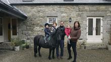 Lorcan Carpenter and Belinda Bielenberg with their children outside their home, which up to two years ago, was used as a barn. The barn dates from 1820. Anna is on Cilla Black, while Lorcan and Belinda carry the twins, Tom and Jessica. Photo: Tony Gavin