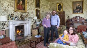 Susan Kellett with her son DJ, his wife Colette and their three-year-old daughter Fearne in the main sitting room, which contains portraits of many of Susan's ancestors. Colonel George Jackson hangs over the mantlepiece. While there has been a family residence on the land for 600 years, Colonel Jackson is the ancestor who in 1798 built the house as it is now. The house is full of antiques like the clock on the mantlepiece, which is a 19th-century boulle clock. Photo by: Tony Gavin