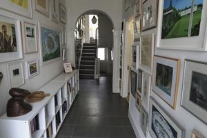Artist Bernadette Madden has created a veritable gallery in her hallway with all the paintings she has picked up through the years at the annual graduate shows at the art colleges