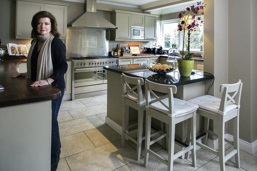 Sharon in her kitchen. The floor is cream porcelain and the units are an oaty shade, with a mix of wooden and granite worktops