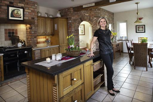 Maureen Harrison in her country-style kitchen. The feature brick wall was her husband Flann's idea, and he used old brick from a derelict farm building. The oak units were made by her brother, Mark McKenna. Photo: Tony Gavin.