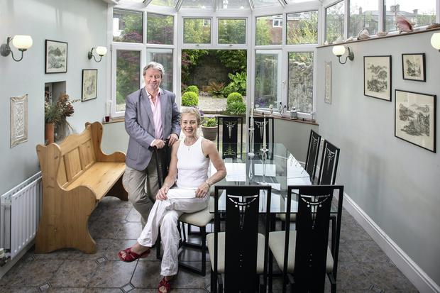 Bill and Susan in the conservatory they added to their period home. They use it as a dining room when entertaining. On one side are steps to the living room and, on the other, doors leading to the garden. Photo: Tony Gavin.