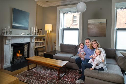 Achim and Catriona Gottstein with their adorable daughters, in the front reception room. The Carrara marble mantlepiece is original, while the windows and shutters were completely restored. The walls are painted grey. Photo: Tony Gavin.