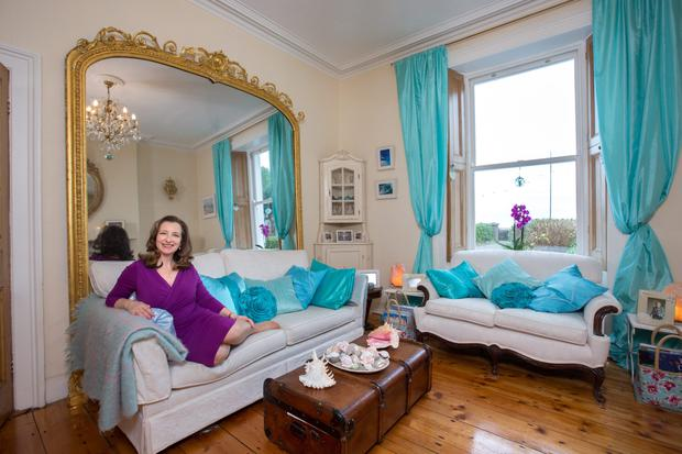 Artist Roisin Fitzpatrick in her living room, which features soft furnishings of aquamarine and bowls of sea shells. 'I wanted to bring the sea into the house without getting the toes wet,' she notes with a laugh. Photo: Tony Gavin.