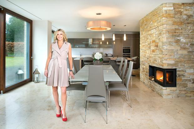 Entrepreneur Louise Jordan in the kitchen; the floor is limestone, the units and dining table are by Kube, and the large shade is by Illumination. The glass doors open out onto the garden. Photo: Tony Gavin