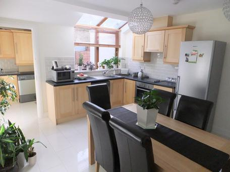 The open-plan kitchen dining area has modern fitted units at both eye and floor level, with an extensive worktop counter and an attractive tiled splash-back