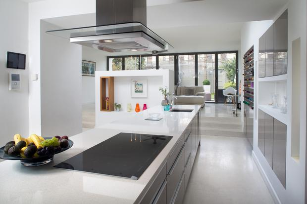 The enormous kitchen has steps up to a light-filled living area where the glass bi-fold doors pull back completely and seamlessly open the room up to the garden.