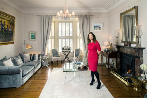 Hilarie in her drawing room, which is decorated in restful greys and creams. Hilarie loves to mix antique and contemporary pieces. She also collects art, and has many paintings by local artist John Short. Photo: Tony Gavin