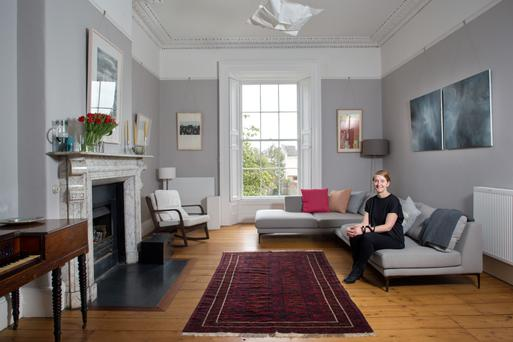 Morwenna in her living room. The seating unit is from Roche Bobois and the diptych above it is by Vera Klute. Photo: Tony Gavin.