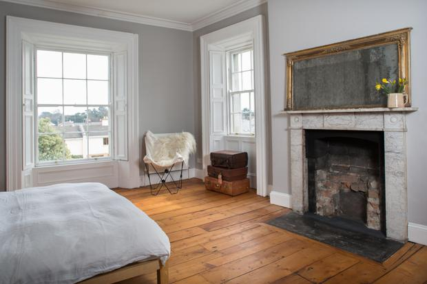 The master bedroom has wonderful views thanks to the unusual corner windows. The mirror over the mantelpiece is from her parents' house and she is waiting to get the right grate for the fireplace.
