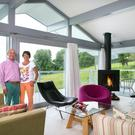 Stan and Ursula in the living area on the upper floor, where the white floor and white walls are offset by pops of colour. The coffee table is by Irish contemporary furniture designer Knut Klimmek