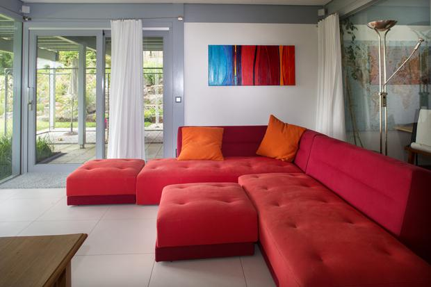 The modular seating in the TV room at garden level is from Ligne Roset, while the colourful painting is by Louth-based artist Patricia Murphy, who lives in Blackrock - Stan and Ursula admire her work. See patriciamurphyartist.com