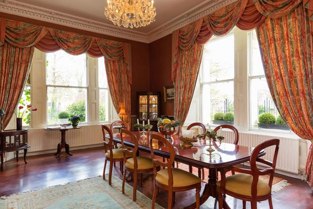 The terracotta-painted dining room has a working marble fireplace