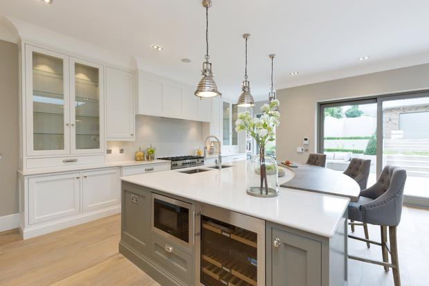 The open-plan kitchen has marble counter tops and a large island unit