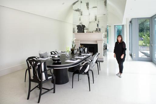 Interior designer Ann Marie Bourke in her dramatic dining area - she had the black and silver table made to suit the space, and she has surrounded it with a mix of Ghost chairs and old mahogany chairs, which she updated by gessoing them in black. The distressed mirror over the mantelpiece draws attention to the height of the ceiling
