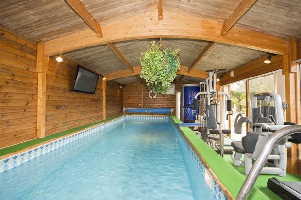 Indoor heated swimming pool and gym room with a big-screen TV