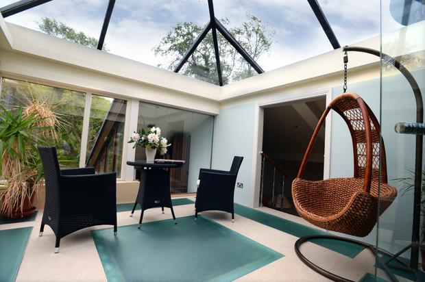 Swinging in the sun: One of the home's internal sun traps with a hanging basket chair to enjoy the light
