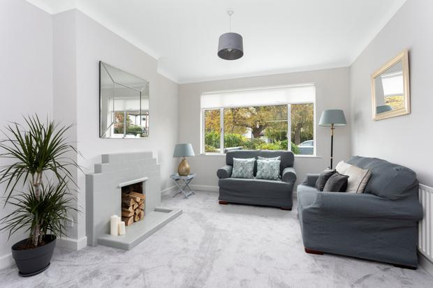 The living room at No49 retains the original mid-20th-century tiled fireplace