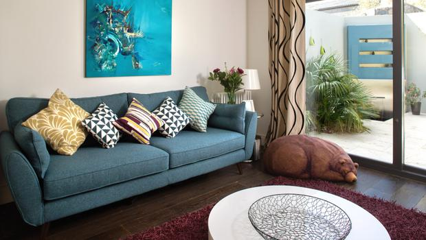 The living room is furnished with blue sofas from DFS, which echo the blue of the fountain outside. The paintings were picked up on travels in Vietnam and Argentina, and cushions of different hues abound. 'I've a bit of a cushion fetish,' says Richard