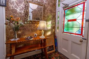 Entrance hall with stained glass door and gilded wallpaper