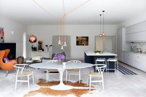 The open plan area with marble dining table, copper lights and limewashed parquet