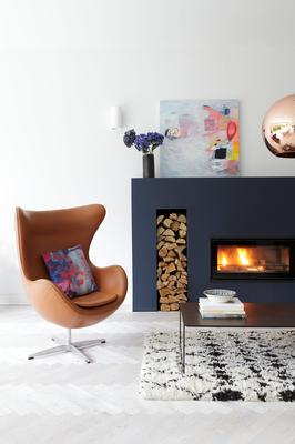 The contemporary fireplace was designed to act as a focal point and highlighted in Farrow & Ball's Hague Blue. The chair is a Fritz Hansen original, also from Nest, while the rug is by Beni Ourain, from Emily's House in London