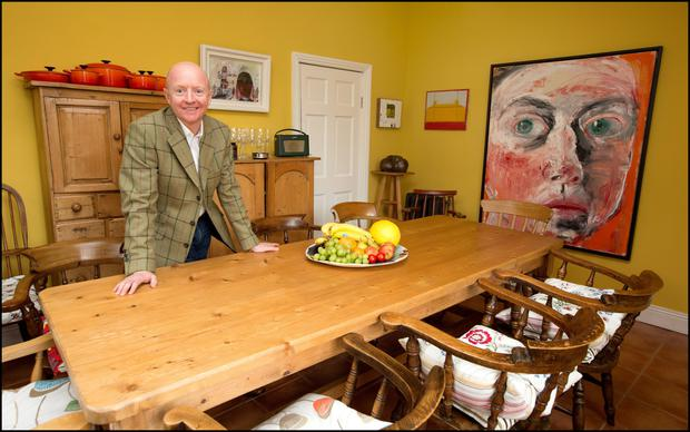 John Daly,owner of the Hillsboro Fine Art Gallery in his pine kitchen. The self-portrait is by Welsh artist Shani Rhys James