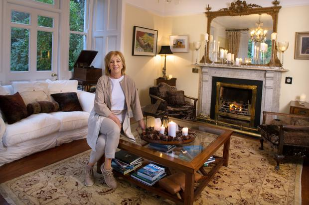 Boutique owner Carmel Brennan in her drawing room. She likes a neutral palette and adds colour with rugs and paintings by Irish artists. The reclining nude above her left shoulder is by Sarah Longley