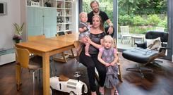 Monika Crowley with her husband, Frank Long, and their two children, Lauren and Karl, in the dining area of the kitchen. The extra large bulb over the table is from Industry. Photo: Tony Gavin