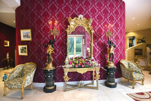 A gilt wood console table and matching mirror in the reception area.