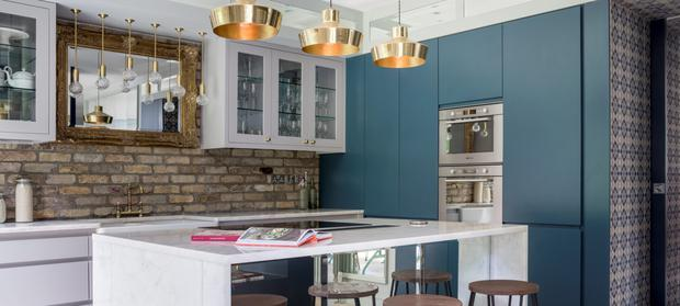 GILT EDGE: Industrial style combined with glamorous touches such as the gilt mirror and brass lighting add drama to this Kingston Lafferty Designkitchen in Ballsbridge.