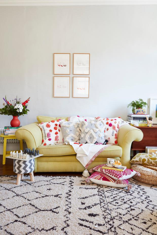 The yellow sofa from Heals was covered in yellow linen by a local upholsterer. Cushions and throw are from Anthropologie. The three-legged stool is from Wilko.com
