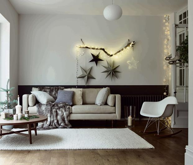 The DFS Marl sofa in stone with white wool floor rug and faux fur throws makes for a Scandi-style Christmas