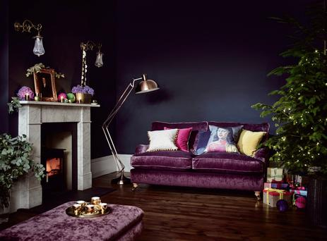 Low-key tree decorations go with the Gower velvet sofa and footstool in aubergine crushed velvet from DFS