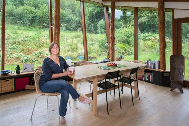 Jo Lewis in the sun room. Rough-cut larch tree trunks hold up the roof, while the many glass panels make for a bright, light-filled space