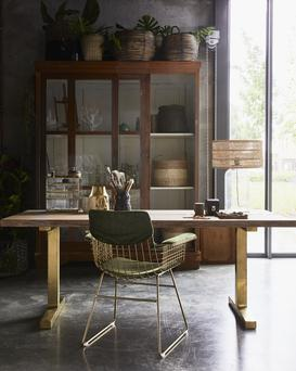 A natural wood table paired with a brass chair makes for an elegant and flexible workspace set up. From a collection at Irish e-tailer home-lust.com